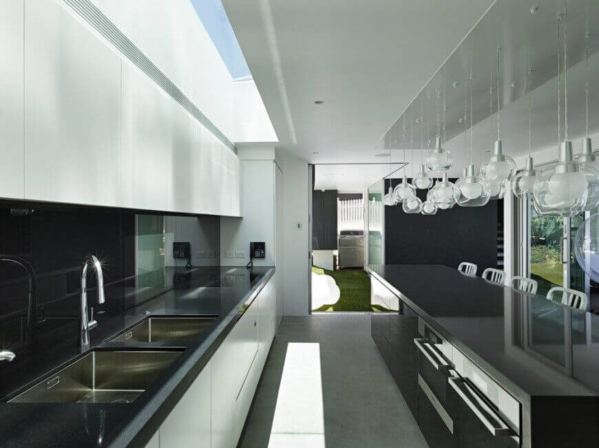 The clean edges in this kitchen are achieved by the basic palette and industrial materials. The light grey of the concrete floor harmonizes the white cabinets and walls with the dark island and countertops. Silver accents in the fixtures, appliances, and barstools adds visual interest while the glass globe pendant lights soften the entire room.