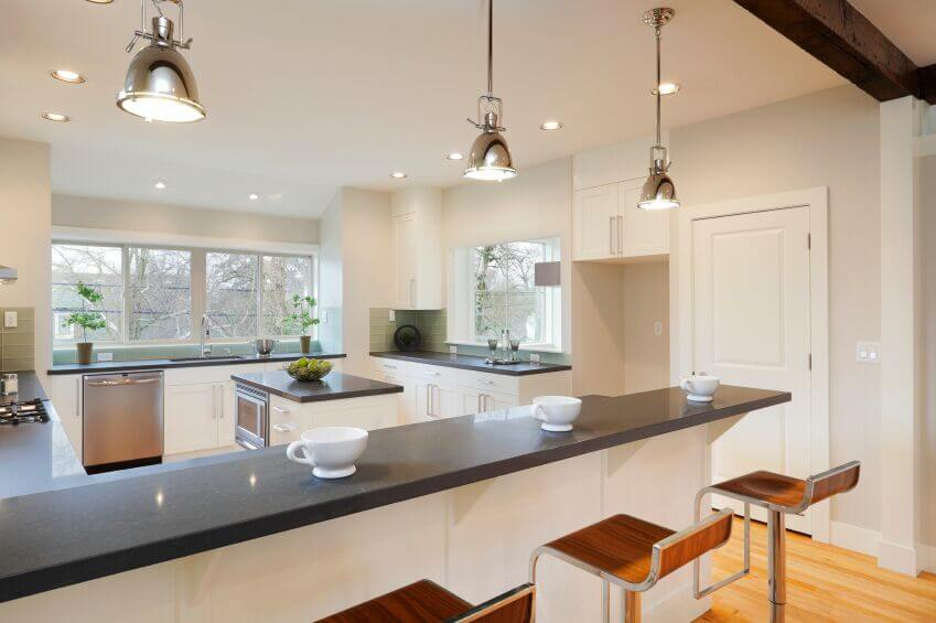 This stunning kitchen breaks up the white and grey theme with the addition of a striking pale green tile backsplash. The expansive countertops soften the reflected light without darkening the room too much while the silver pendant lights complement the appliances and hardware of the cabinets. The warm barstools add an extra pop of color that harmonizes with the light wood floor.