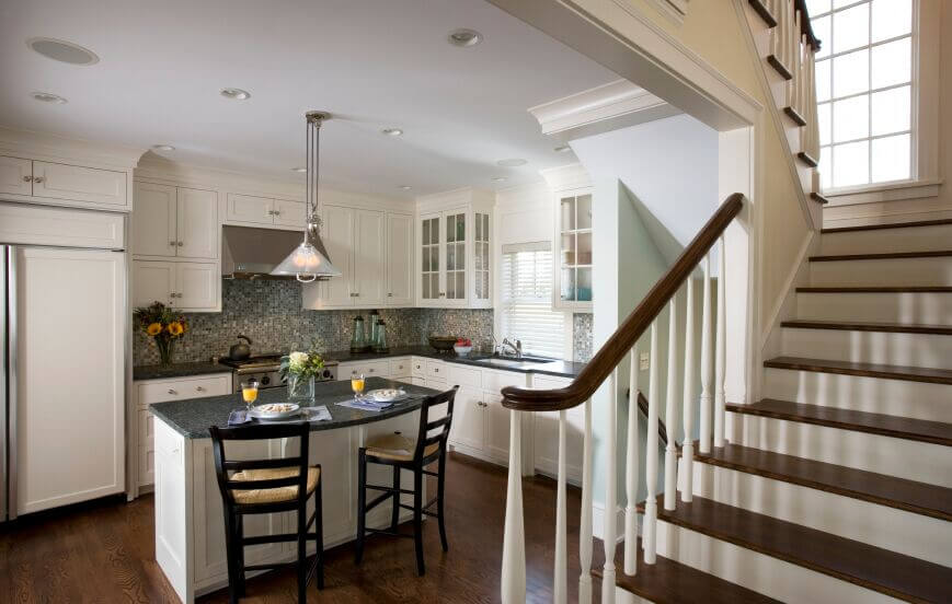 This quaint kitchen expands itself with the use of white cabinets and matching fridge doors. The blue-green granite balances the use of white while adding a touch of color also seen in the tile backsplash. The stunning dark wood flooring complements the kitchen while also continuing through the rest of the house.