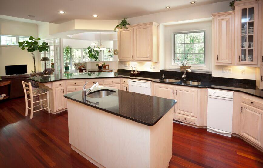 This lovely kitchen continues the bright, open feel apparent in the rest of the rooms. Utilizing warm, off-white cabinets enriches the bright red of the wood floor while the grey granite breaks up the space.