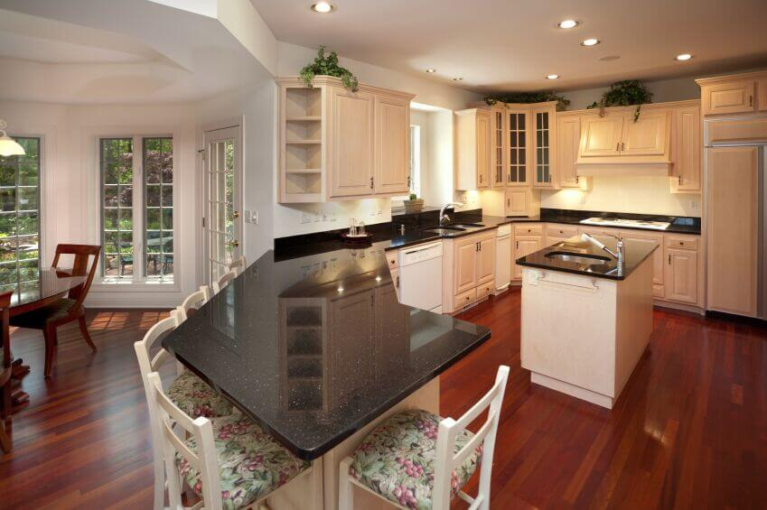 This angle shows off the granite bar and displays the flow of the rest of the kitchen offered by the angled counters. With plenty of prep space and easy access the stove, fridge, and sinks it would be easy to move through this kitchen.
