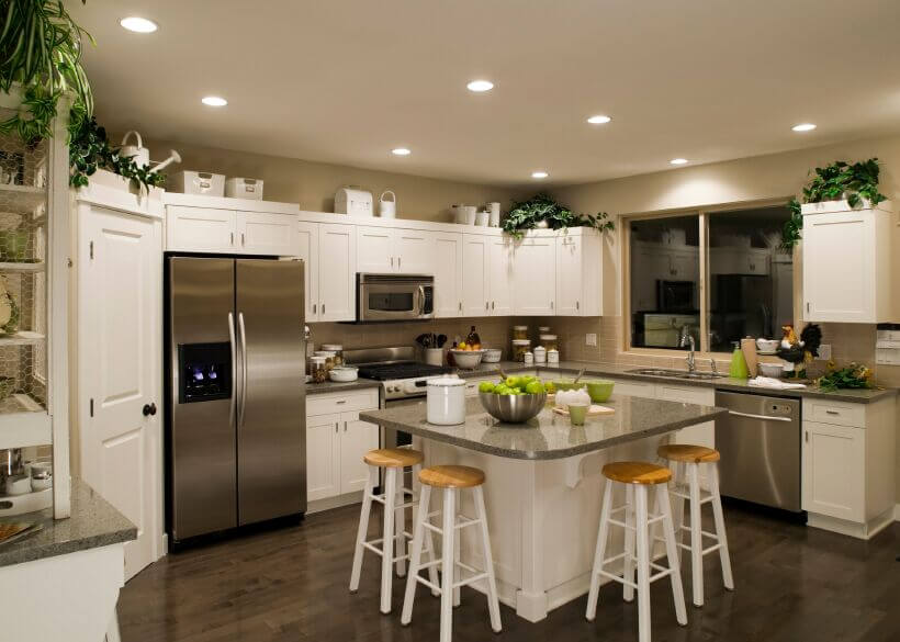 Choosing counter tops to complement both the appliances and the beautiful wood floor gives this kitchen a sense of unity and cohesion. Bright green accents and plants bring simple pops of the color while the white cabinets keep the room bright, even at night.