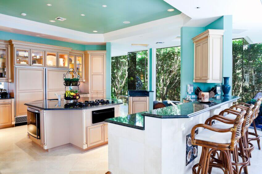 This refreshingly bright kitchen is a fun example of how to use color and keep your kitchen feeling open and inviting. The warm wood cabinets achieve the same light feeling of white cabinets without continuing the same trend. Instead, using white as an accent color in the bar and ceiling makes the room feel larger and doesn't wash everything out.