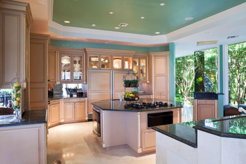 The shape of the dark granite counters mimics the octagonal shape of the island and creates a natural flow around the room. Using the blue wall color in the recessed ceiling while bordering it in white bring interest up to the ceiling without making the room feel smaller or darker.