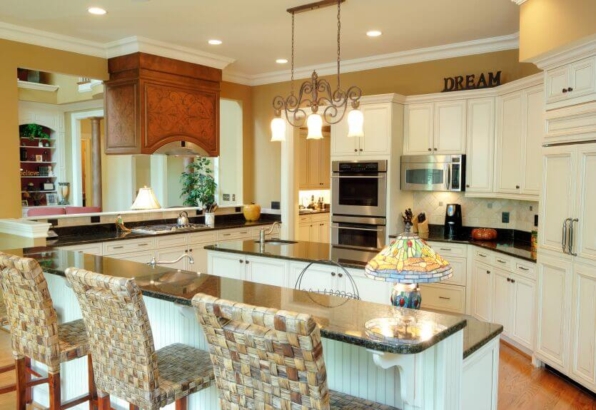 This warm, cozy kitchen is achieved with the use of golden walls and off-white cabinets. The dark counters complements the appliances while the gorgeous woodwork around the stove hood plays focal point to the rest of the room.