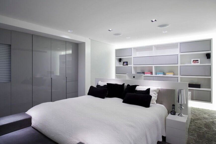 In a sleek, ultra-modern bedroom defined by white, the central bed rests against a unique built-in desk design. Behind that, we see a fantastic array of bookshelves filling the entire wall, featuring both closed and open compartments.