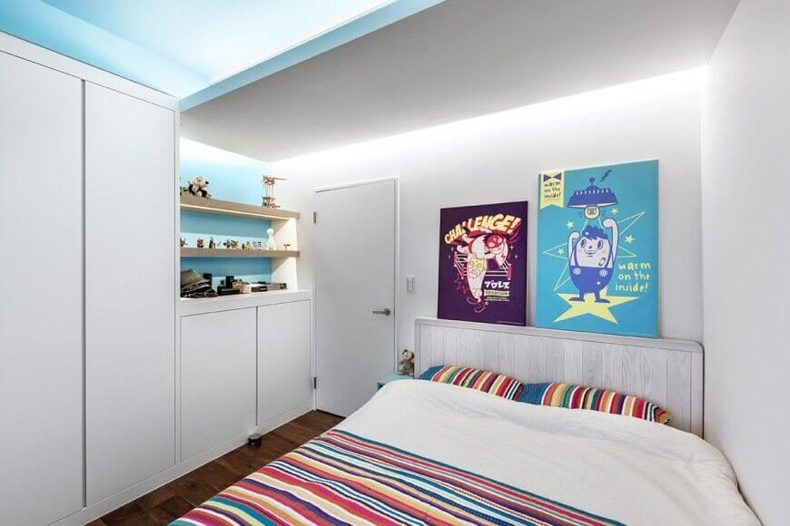 This children's bedroom punctuates the monolithic whiteness of the walls with splashes of sky blue on the ceiling and behind the subtle built-in bookshelves. The shelves themselves appear in natural wood, with built-in lighting.