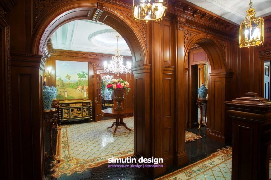 Pulling back, we see that the arch is actually part of a pair that leads into another mosaic tile floor room with a grand staircase to the second floor.