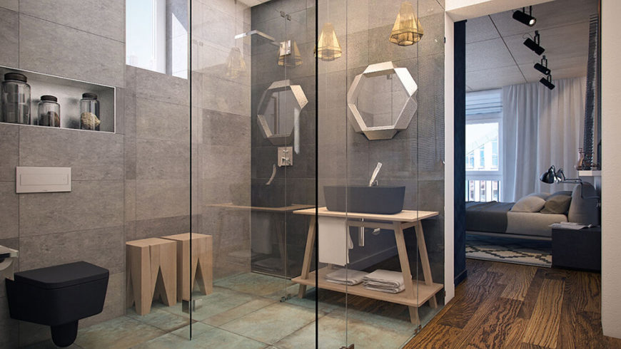 This beautiful bathroom features a glass enclosed shower and sink area. The lovely grey tile walls brighten the bathroom without taking away from the palette of the rest of the house and more natural wood can be found here. Oxidized copper sheets make up the floor of the bathroom.