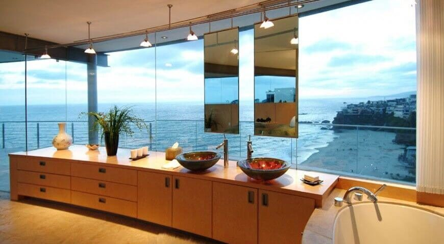 This incredible glass-wrapped bathroom uses the magnificent view as all the decoration it needs. Twin narrow mirrors are hung from the ceiling as a necessity, to avoid blocking the wonderful view.
