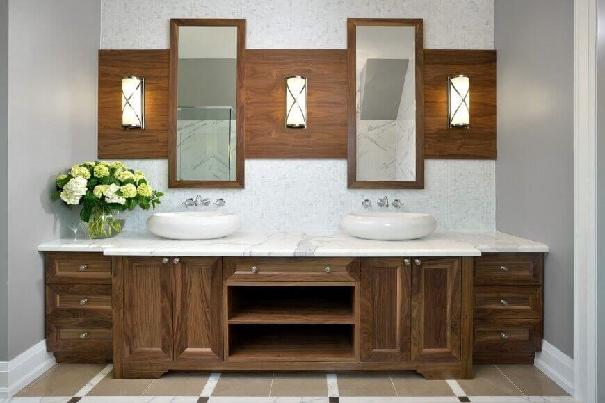 A simple yet elegant wood vanity with a rich wood grain matched with white marble countertops. A wide panel of wood plays host to three light fixtures and two lengthy mirrors. The smooth curvature of each vessel sink adds to the contemporary charm of the space.