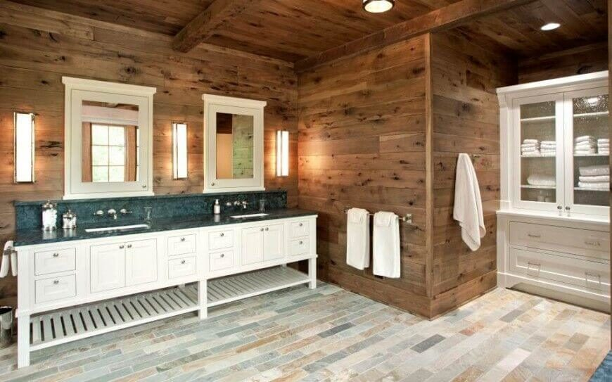 Contemporary multi-tonal tile floors are paired with rustic wooden walls. Country-style sinks and mirrored medicine cabinets create a fully functional and stylish primary bathroom.