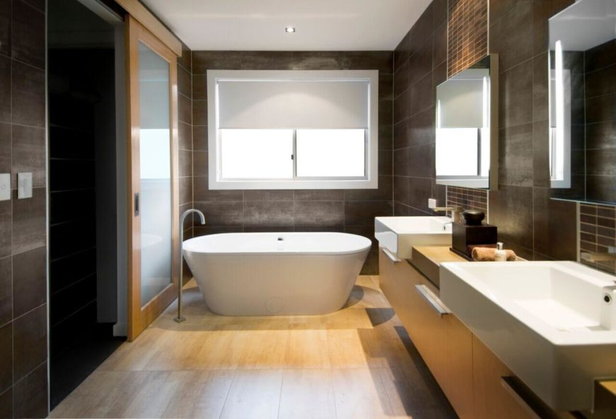 While similar to the above bathroom in color pallet and in materials, certain aspects of this modern bathroom give it a different cast. For example, the free-standing soaking tub gives the space a more minimalist feel than the large, enclosed jacuzzi tub of the previous room.