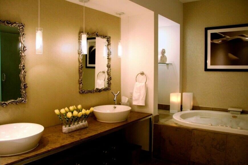 A trio of small pendant lights cast soft light into the pair of ornate gilded mirrors above the modern vessel sinks with chromed faucets. The mixture of traditional and modern is striking and utterly luxurious. Added accents like the floral arrangement between the sinks and flameless candles by the tub take this space to the next level.
