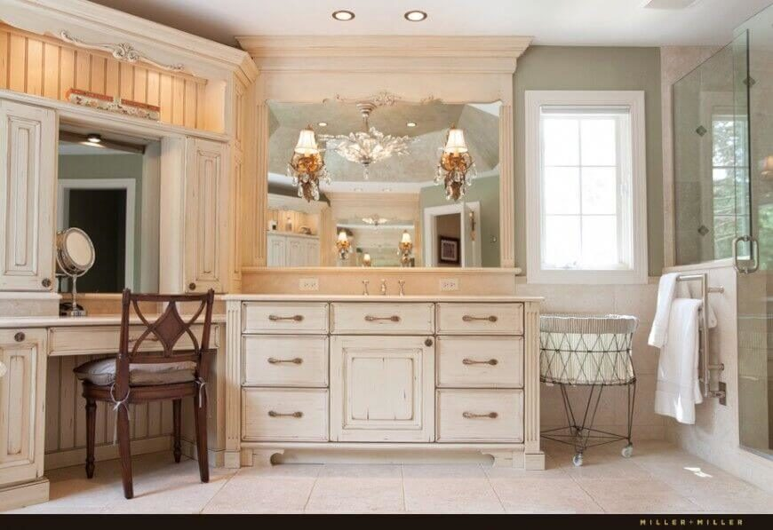 The large mirror above the distressed rustic-chic vanity is built into the ornate frame that reaches to the ceiling. To the left is an angled makeup table with a framed, inset mirror, along with a smaller makeup mirror with magnification