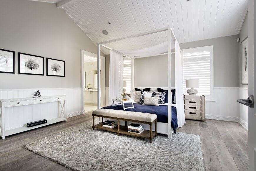 This gorgeous contemporary bedroom accentuates the high ceilings with a lovely white canopy bed. The antique trunk style nightstand is a simple but elegant touch.
