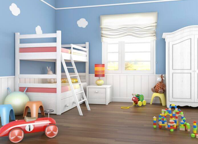 The white furniture in this room allows the muted blues and bright accent colors to pop, creating a whimsical color scheme befitting a child's room.