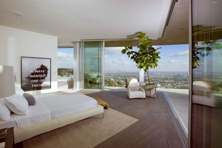 This understated bedroom allows for great views of the surrounding cityscape. The use of white furniture ensures not to distract from this beautiful view.