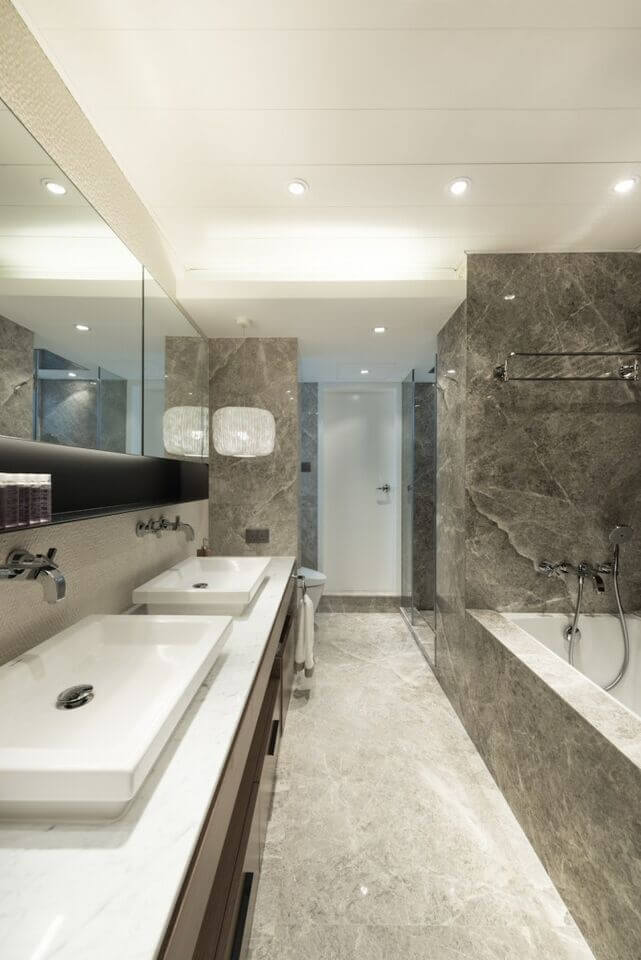 Gorgeous gray marble offsets the dark wood and white accents. The dual vanity running along one side of the bathroom hides the toilet on the far end, across from the glass doored shower. The tub stands to the right, encased in more gray marble.
