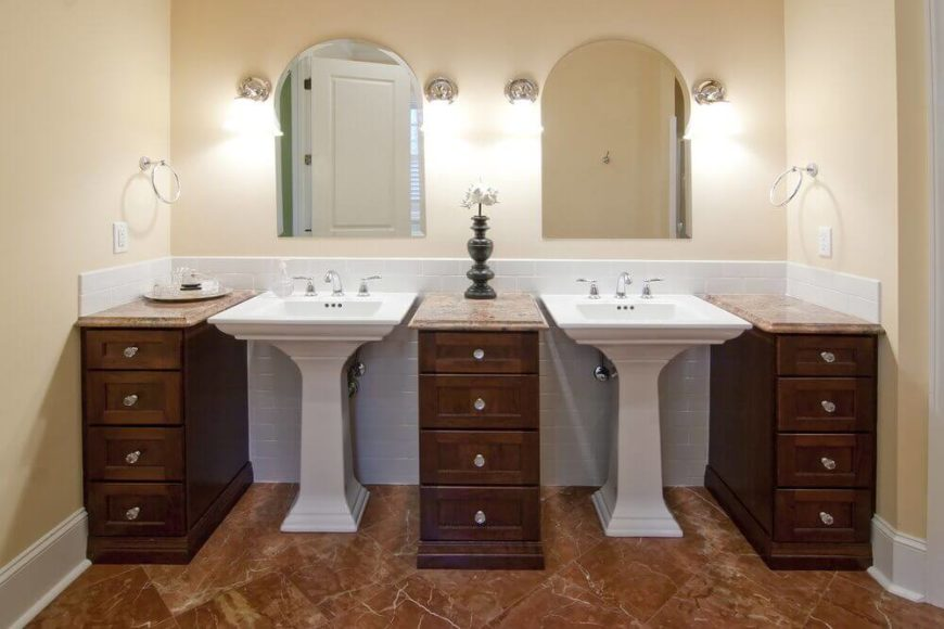 These lovely white pedestal sinks are broken up by the installation of gorgeous wood drawers - offering storage and a contrast of color. Marble floors and arched vanity mirrors conclude the look of this contemporary bathroom.