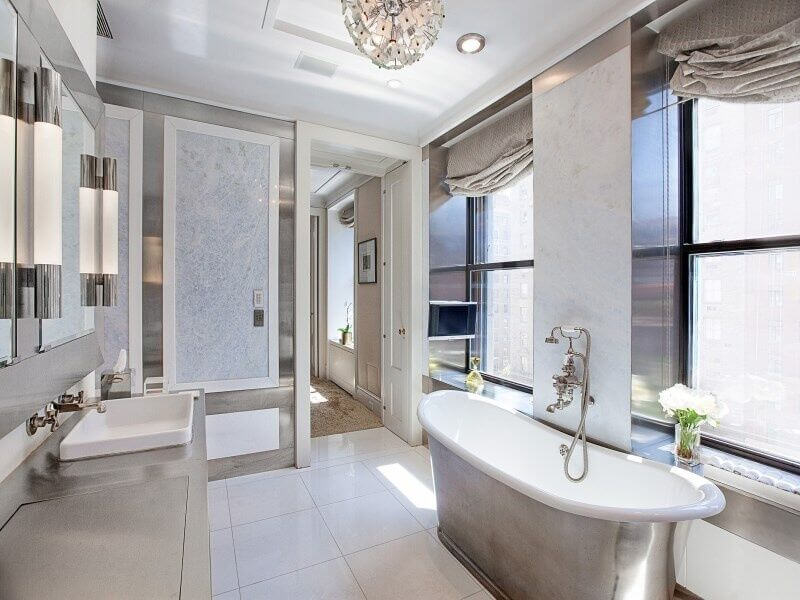 Silver accents complement the pale colors used in this bathroom. The shallow white square sink and freestanding soaking tub are pulled together by the white tile floor and white trim. A lovely and unique pendant light tops off the room.