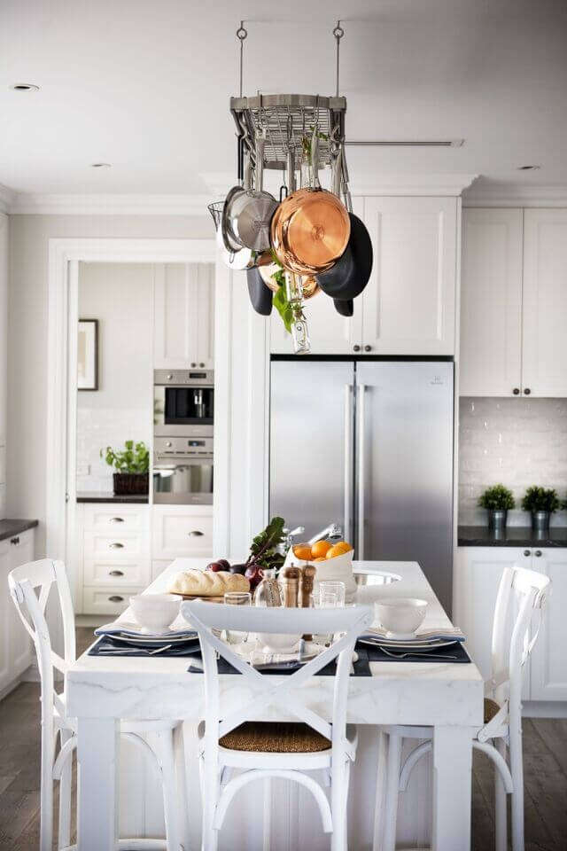 This lovely stainless steel pot rack is a great addition to this contemporary kitchen. The balance of black, white, and silver makes for a striking design.