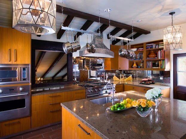These sleek pot racks match the use of silver throughout this eclectic kitchen. Geometric lights, a mirrored stove hood and dark, exposed beams make for an interesting combination of design elements.
