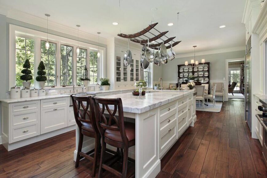 Luxurious modern kitchen with elegant pot rack hanging over the marble topped island.