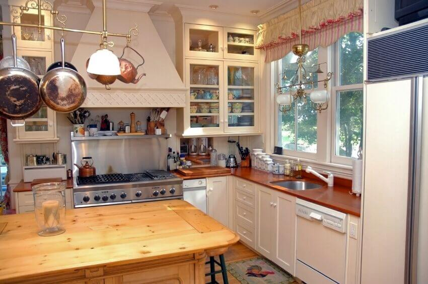 This cozy kitchen utilizes and single bar as a pot rack instead of the more common ring or rectangle. The lights on either end of it match the light fixture over the sink to tie the whole kitchen together.