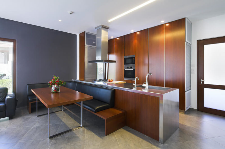 The kitchen is awash in sleek wood paneling and stainless steel, for a modern look that nods toward tradition. The room features a large breakfast nook with an L-shaped bench set against the island.