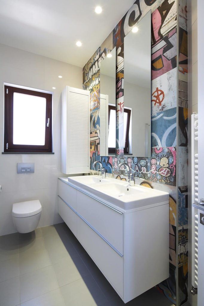 The bathroom is where a burst of wild creativity happens. Instead of clean white surfaces all around, it sports a unique graffiti wall with a mosaic of beautiful, colorful, and strange imagery backing the vanity.