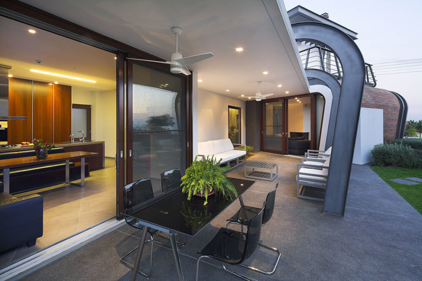 Moving back outside, we see the modern patio furniture standing beside the large sliding glass panel that connects the kitchen to the outdoors. This area is hugged by the L-shape of the structure for a wealth of privacy.