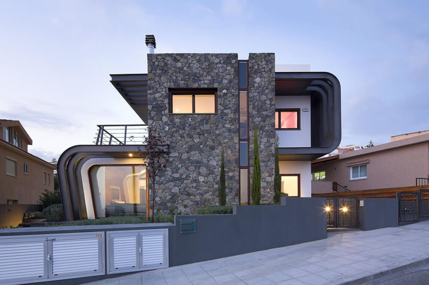 With the interior glowing out through large windows, we can appreciate the complex arrangement of space within the structure, perfectly disguised by the mixture of stone, steel, and concrete surrounding the home.