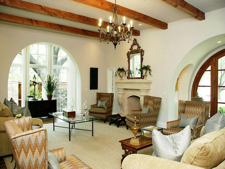 This traditionally appointed living room in all white features a rich array of furniture and a marble fireplace, sharing space below a white ceiling with natural wood exposed beams.