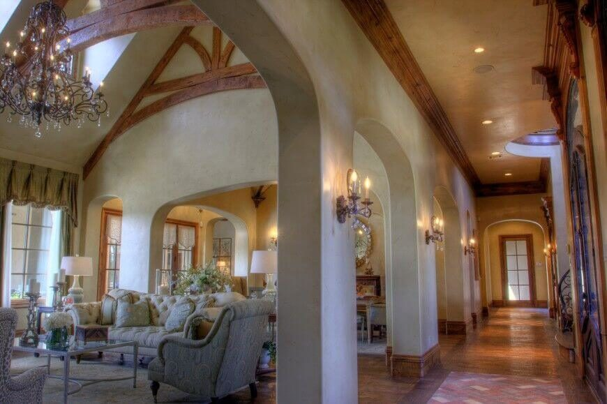 Elegant arched entryways perforate the walls of this immense living room. The double height vaulted ceiling in beige contrasts with rich natural wood exposed beams.