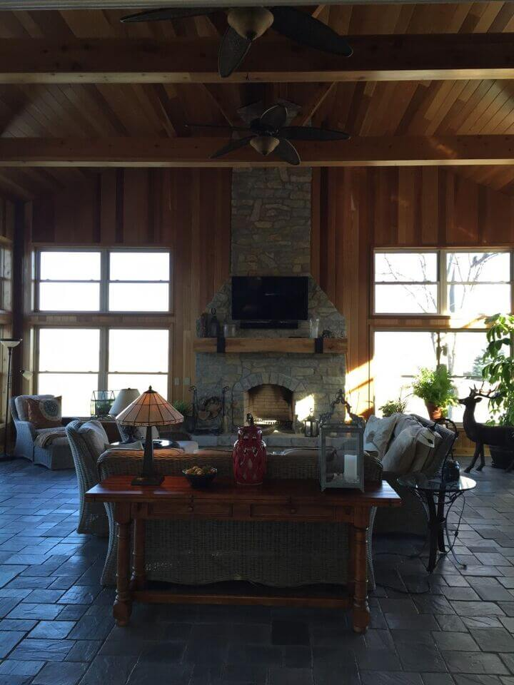 Here's another double height living room, centered on a stone fireplace. The dark tile flooring contrasts with rich wood walls and ceiling, while exposed beams hang between propeller styled ceiling fans.