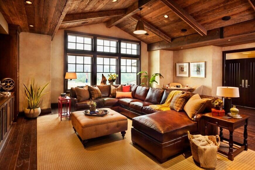 Rich natural wood flooring and ceiling sandwich this large living room, with matching exposed beams. A massive leather sectional wraps a button tufted ottoman at center.