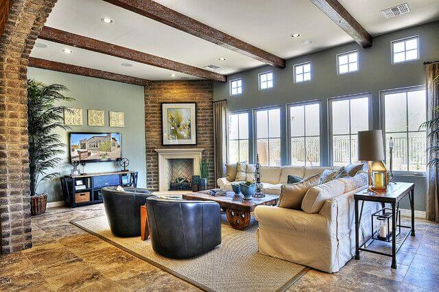 Large format tile flooring underpins this living room beneath a set of massive windows and a white ceiling with exposed natural wood beams.