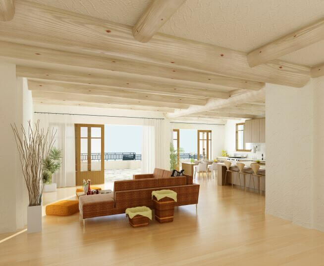 In this expansive open-plan room, the living room glows with the warmth of hardwood flooring and bright wood curved beams crossing the ceiling. Large openings toward a balcony blur the line between indoors and out.