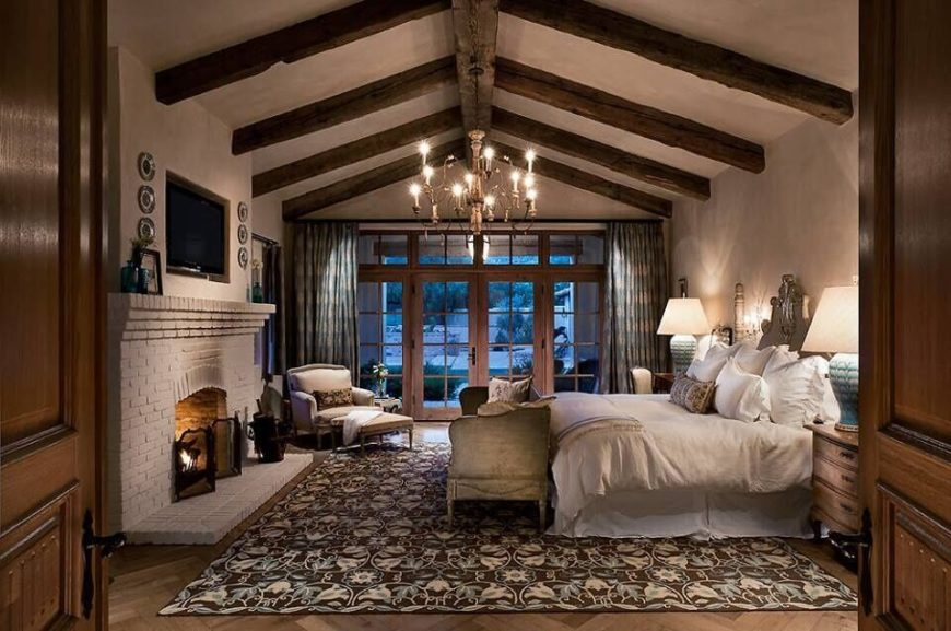 This gorgeous primary bedroom has high ceiling with stunning rustic wood work. It's egg shell white old brick fireplace has a cozy television nestled into the wall above it.