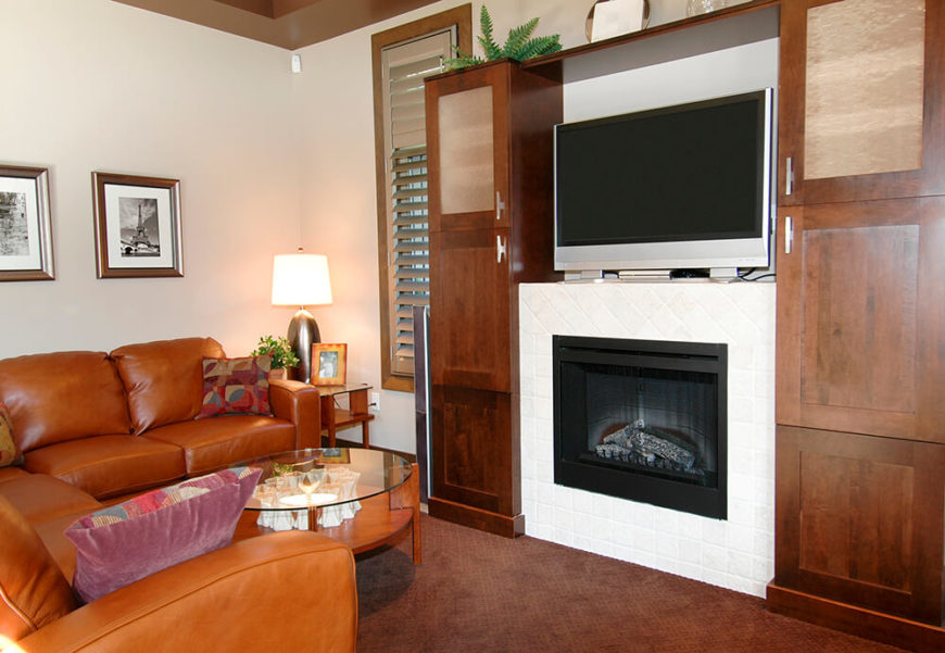 This set is nuzzled into an natural dark wooden entertainment center. The face of the fireplace is flat and made of a smooth white brick. The mantle holds the television on it's own without having to secure the TV in place.