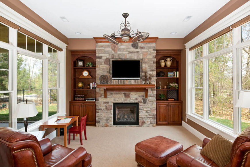 This marvelous stone fireplace has a wooden mantle just under the television for extra storage space. The stone construction is accented beautifully with all natural wooden pieces for a simple contrast.