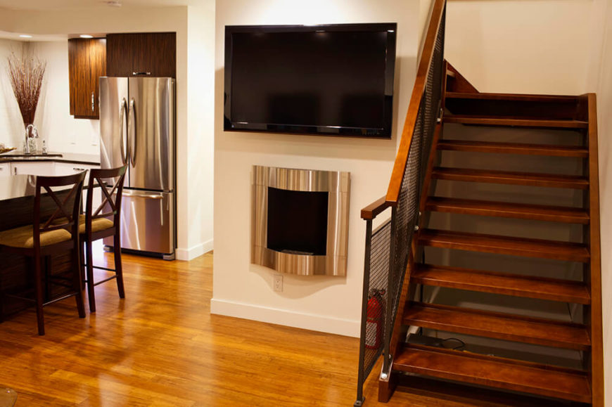 This TV and fireplace and in an interesting spot in the home. Placed between the foyer and the kitchen, they add some convenience to watching the news in the morning as you get ready, and some warmth by the front door. The fireplace is made of brushed steel for a truly modern theme.