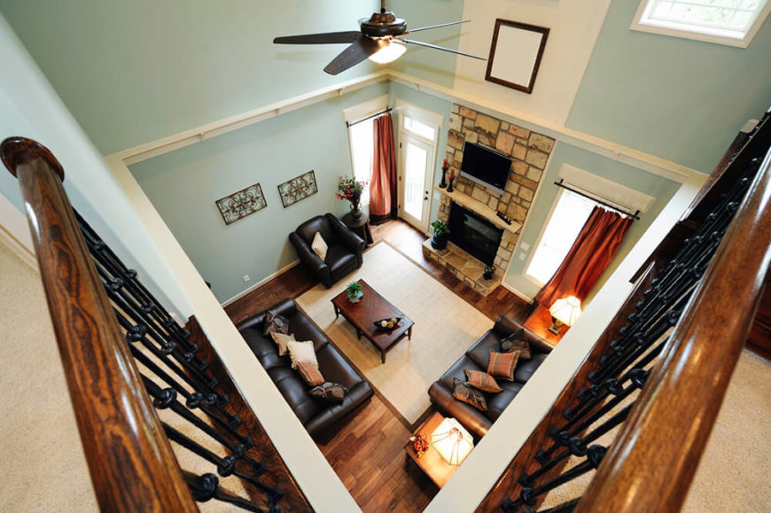 Here we can see an eagle-eye view of the living room on the first floor. A stone fireplace extends upwards to encase the flat screen TV and include it in the center decor.