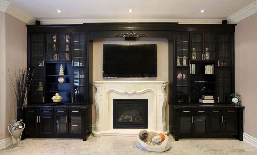 An entertainment center surrounds the plaster fireplace and the television that is mounted above it. The delicate details in the mantle add subtle luxury to the view.
