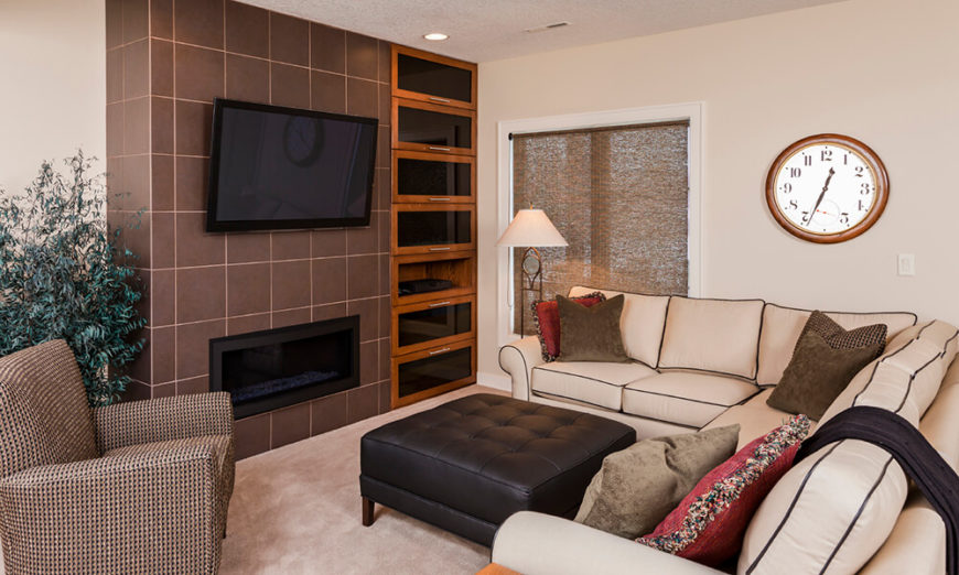 This modern living room has a television and fireplace that are inconspicuous. The attention of the room is not drawn to either one, and the room can be seen as a whole.