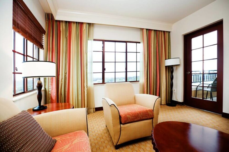 Multi-colored curtains add warmth to the light color pallet, and lengthen the walls.