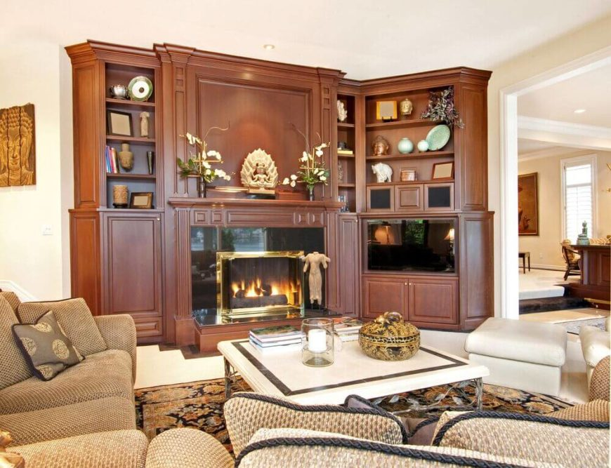 Exotic sculptures and artwork are displayed on the mantle and shelves surrounding this fireplace and entertainment center.