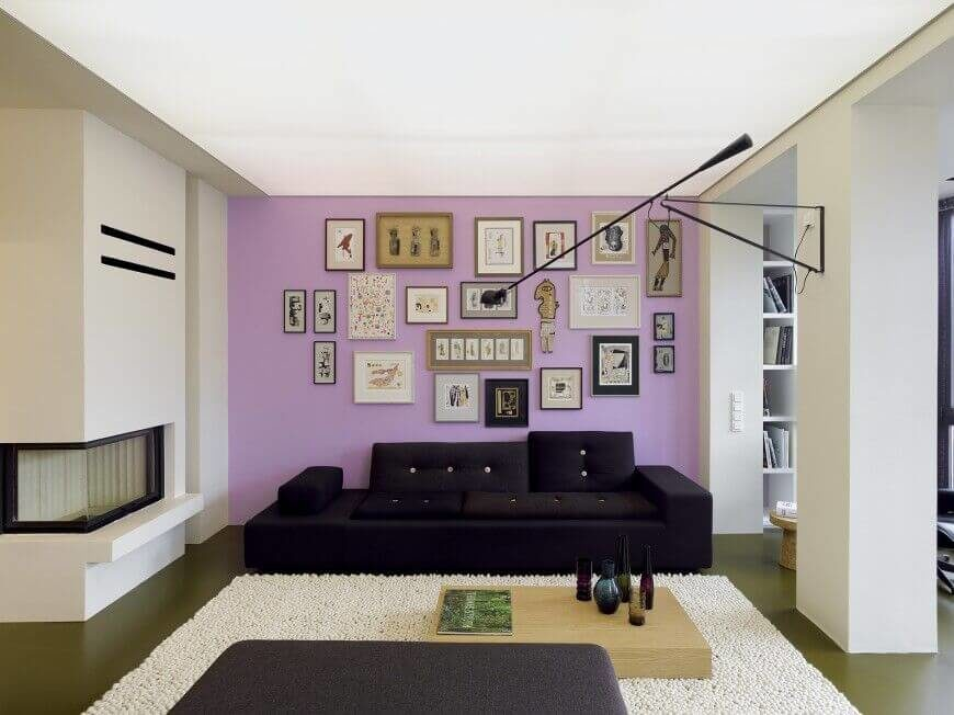This light lavender accent wall is filled with an array of prints and artwork that take up nearly the whole wall.