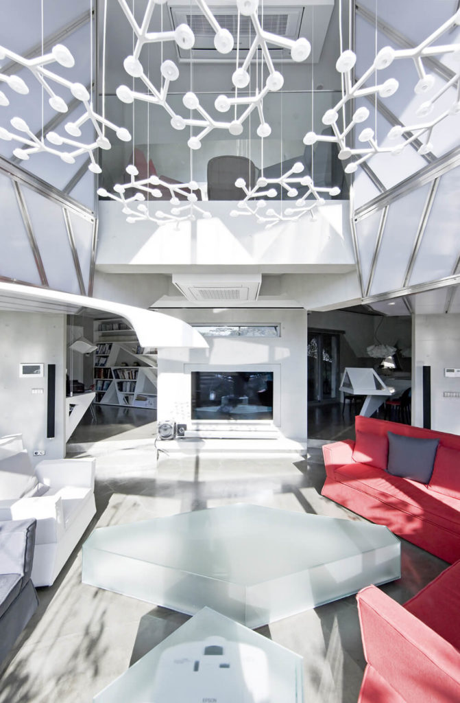 In addition to the soft red sectional and white walls, a novel textural element enters this space in the form of smoked glass coffee tables. Overhead, an interconnected set of lighting mimics the look of tree branches.